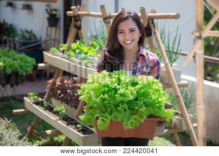 happy young woman holding a bucket full of lettuce in front of her urban farm