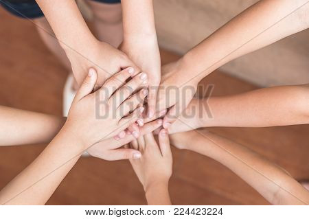 School kid teamwork volunteer's hands for friendship, student's team work togetherness, children's day and community collaboration concept