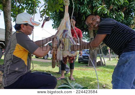 Keningau,Sabah-Sept 1,2017:Muslim butchers trimming a buffalo cow meat to be distributed to muslims in needs during Eid Al-Adha.It is one of the holiest days in the Islamic calendar when the major pilgrimage takes place in Mecca,Saudi Arabia.