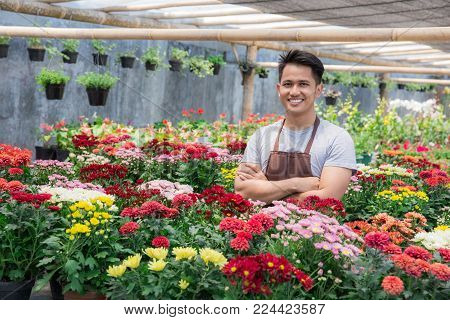 Happy asian male florist working flower gardening shop