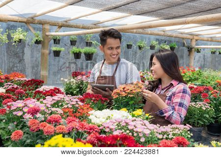 two asian man and woman florist discussing in flower shop
