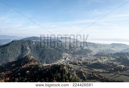 autumn mountain countryside with hills, meadows, colorful forest, blue sky with mist in valleys in Slovakia - view from Hricovsky hrad castle riuins