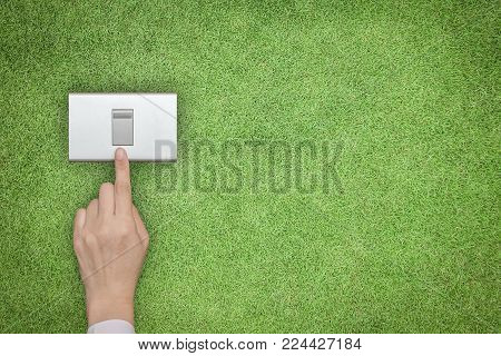 Energy Saving And Ecological Friendly Concept With Hand Turning Off Switch On Green Grass Lawn