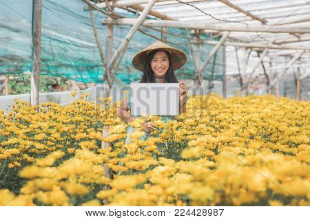 portrait of asian young woman in a flower farm holding blank white board