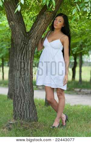 Portrait Of A Girl Standing By A Tree