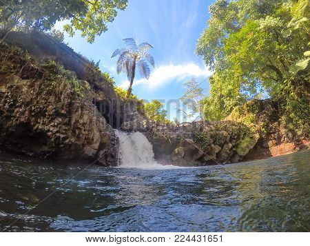Water flowing into swimming hole at Togitogiga Waterfall on Upolu Island, Samoa, South Pacific. Lush tropical foliage and trees.