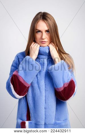 Close-up of a young dark-haired woman in a blue fur coat made from natural mink fur on a white isolated background