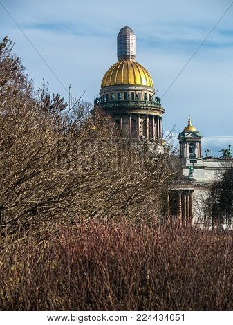 The monumental St. Isaac's Cathedral on the square in early spring in April with a dome in restoration on a warm sunny day in the city of St. Petersburg, Russia