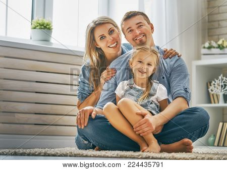 Happy family. Child daughter with father and mother. Mum, dad and girl laughing and hugging. Holiday and togetherness.