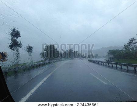 Driving in rain. Road view through car windshield with rain drops Driving in rain.
