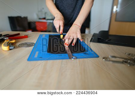 Student learning to sew zipper on purse, future seamstress preparing to do delicate work under direction of experienced teacher. Concentrated girl wearing grey T-shirt sitting near table with quantity of tools.