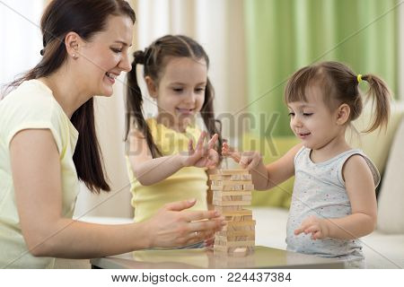 mother and children daughters are playing with board game
