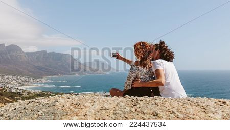 Couple sitting on the top of mountain and taking selfie. Young man and woman sitting together outdoors on cliff taking self portrait with mobile phone.