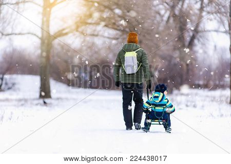 Father and son with a sledge outdoor in the snow, snowing