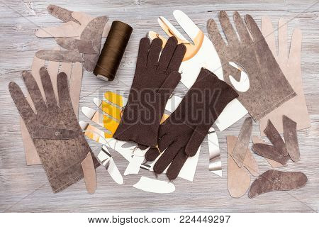 workshop on sewing gloves - top view of various items for gloves production on wooden background