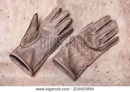workshop on sewing gloves - top view of new hand-made gloves on original natural leather background