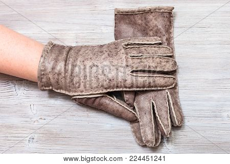 workshop on sewing gloves - top view of female hand in new hand-made glove on wooden background