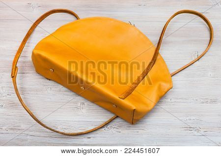 back side of handmade yellow leather bag on wooden table