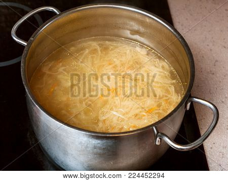 cooking soup - cabbage soup with stewed sauerkraut in steel stockpot on ceramic cooker