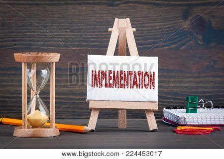 Implementation. Sandglass, hourglass or egg timer on wooden table showing the last second or last minute or time out