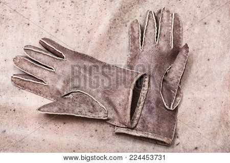 workshop on sewing gloves - top view of new hand-made sewn gloves on original natural leather background
