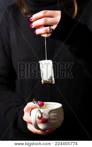Female hands taking out teabag close up
