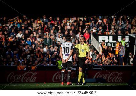 VALENCIA, SPAIN - JANUARY 27: Parejo and Referee talk during Spanish La Liga match between Valencia CF and Real Madrid at Mestalla Stadium on January 27, 2018 in Valencia, Spain