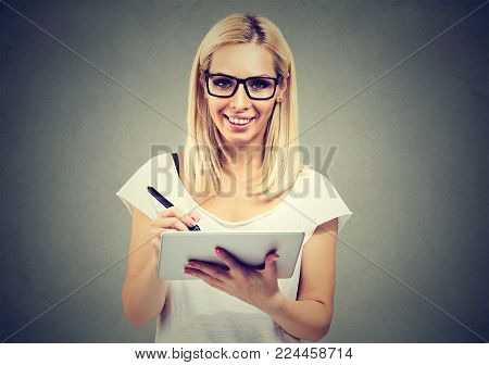 Closeup portrait of a cheerful woman working with stylus and digital tablet pc