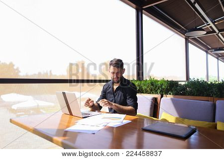 Tired quantity surveyor working at cafe table with diagram and statistic documents. Persistent man dressed in classic black shirt sitting at sofa near green indoor plants. Concept of  preparing estimates and costs of work, keeping track variations