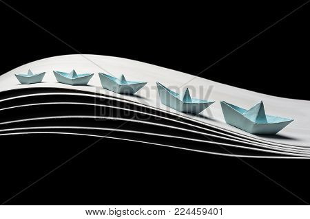 a team of five blue paper boats in the dynamics on the waves and on a black background. 5 blue ships of different sizes