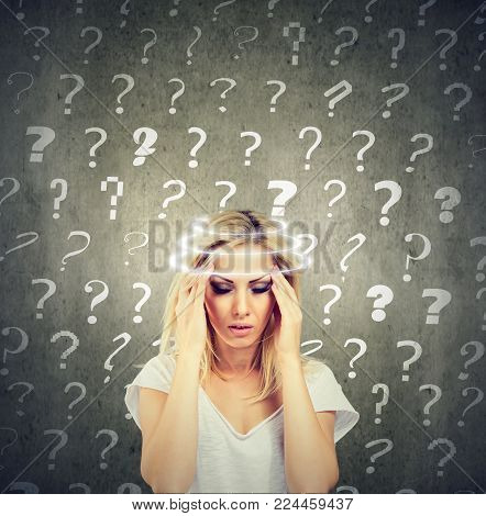 Portrait confused thinking young woman with vertigo dizziness has many questions isolated on gray wall background. Human face expression