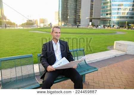 Businessperson reading newspaper and looking at watch outdoors in  . Concept of having break, resting and mass media. Prosperous man wears dark suit with white shirt.