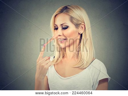Young woman having prolonged nose of creative liar posing on gray.