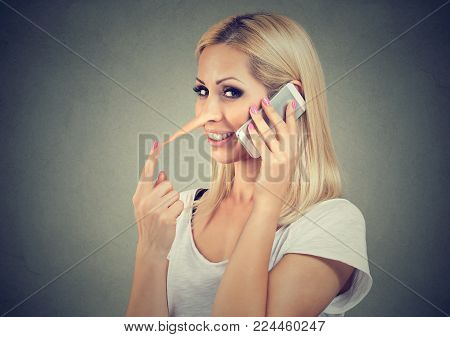 Happy blonde woman with long nose talking on mobile phone telling lies isolated on gray background. Liar concept.