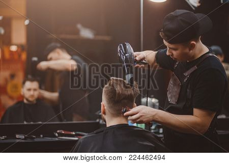 Master stacks hair of men hairdryer in barbershop, hairdresser makes hairstyle for young man. Barber shop. Light. reflection in mirror