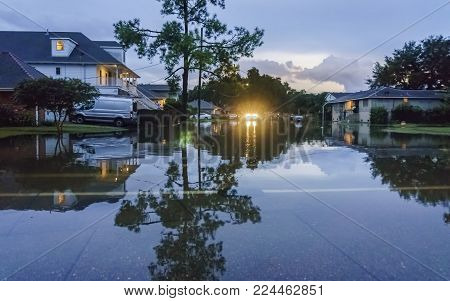 New Orleans, USA - Aug 16, 2017: Flooding on a street in the Lakeview area, 12 years after Hurricane Katrina. Taken from a moving car in low light.