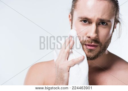 Young bearded  man looking to camera while holding bath towel in hand close to his cheek,  isolated on white