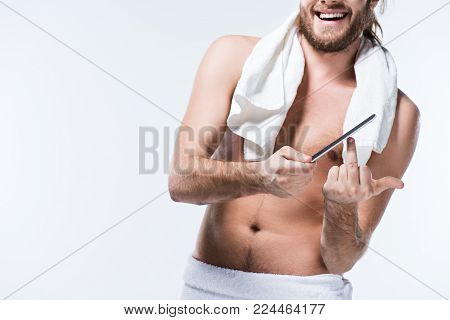 Smiling young man with bath towel around his neck holding nail file in hand and showing middle finger by another one,  isolated on white