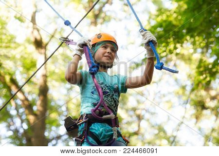 Cute girl moves along obstacle course in rope adventure park against the background of green foliage. Close-up view