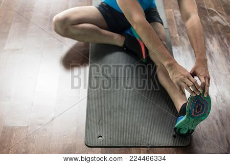 High-angle view of the hands of a man, touching his toes from sitting position as a stretching exercise for flexibility at home or at the gym