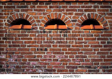 Three symmetric semicircular vent windows on vintage terracotta brick wall. Beautiful texture background in red tones