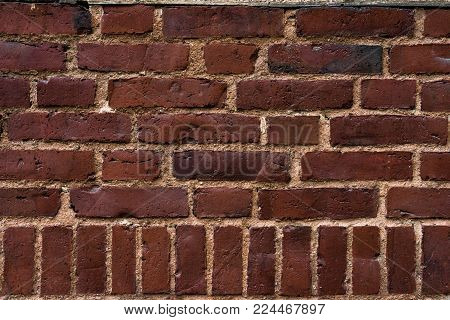 Weathered texture of old dark brown and red brick wall background. Clear texture with scrapes and marks of the past times