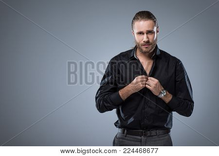 handsome man looking at camera while buttoning up his black shirt, isolated on gray