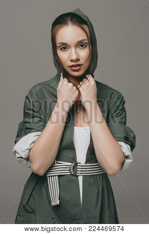 stylish young girl posing in autumn raincoat, isolated on grey