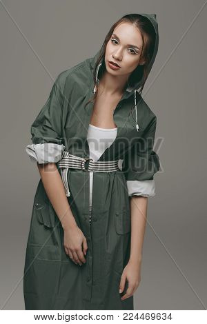 stylish girl posing in green autumn raincoat, isolated on grey