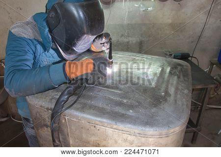 Man welding aluminum construction with TIG welder. Argon aluminum welding