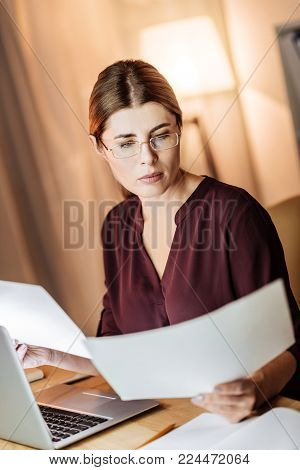 Love my job. Pretty businesswoman wearing glasses and turning head while comparing papers