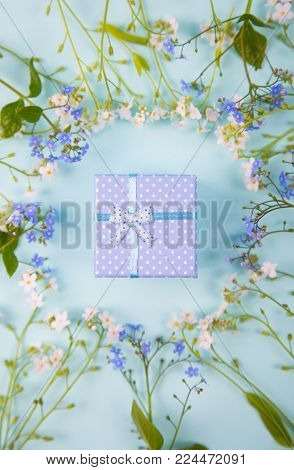 Blue Gift Box Surrounded With Blue And White Little Flowers On Light Mint Background.