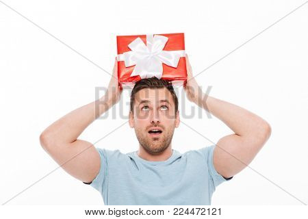 Photo of muscular guy in casual having fun and putting red gift box with ribbon bow on his head isolated over white background