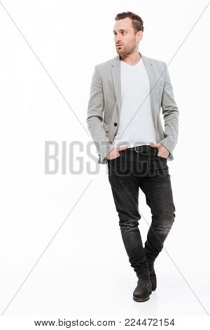 Full-length image of brunette businessman in jacket confidently posing on camera with hands in pockets and looking aside isolated over white wall